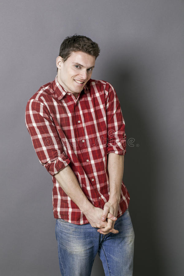 Embarrassed young man smiling for shyness in love question royalty free stock photos