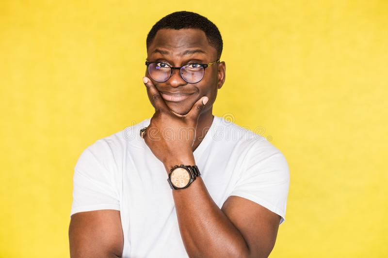 Embarrassed unsure African American man with glasses holds his chin and purses his lips, looks incredulously, tries to stock photos