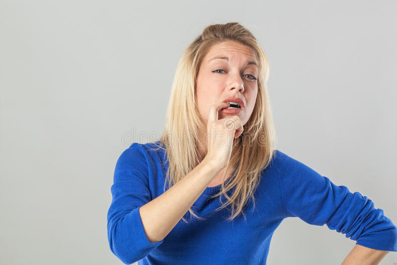 Embarrassed young blond woman making a mistake, being anxious stock photography