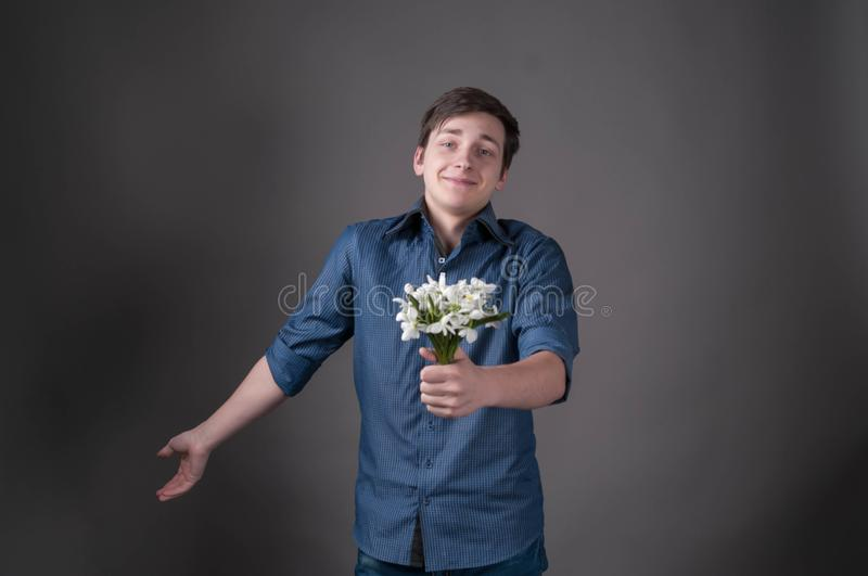 Embarrassed young man in blue shirt holding bouquet with snowdrops, looking at camera and smiling. On grey background with copy space royalty free stock image