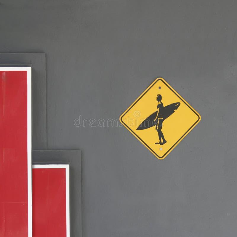 Emblème surfant sur le mur gris de ciment avec les éléments minimaux rouges et blancs photographie stock libre de droits