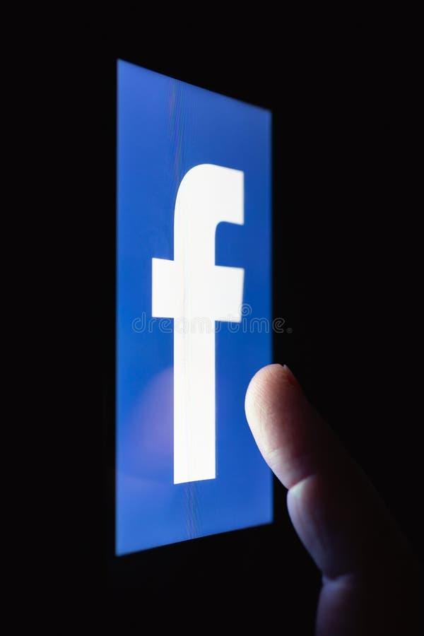 Embleem van Facebook De vinger boven het aanrakingsscherm Het concept afhankelijkheid van populair sociaal netwerk royalty-vrije stock afbeelding