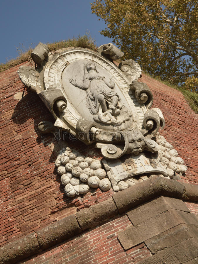 Emblem. Detail of Lucca's medieval defensive wall with an emblem decorating it. Since medieval age, the city has been enclosed by a big defensive wall that still stock image