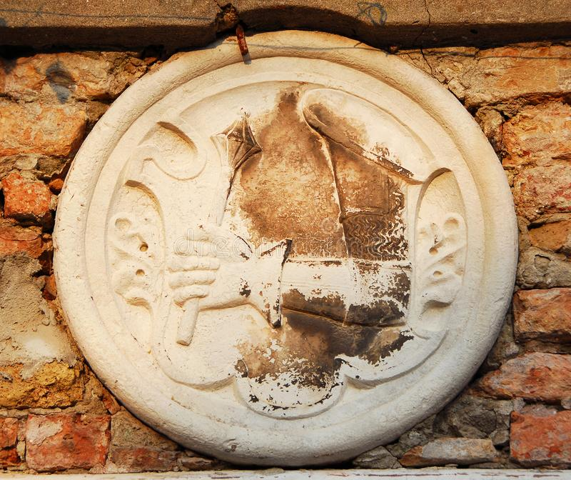 Emblem with mace. Emblem with an armored hand holding a medieval mace, old relief on wall in Venice royalty free stock images