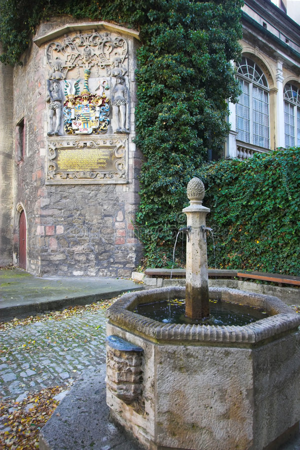 Emblem on the wall and fountain. Medieval university emblem and stone fountain in Jena, Germany stock photo