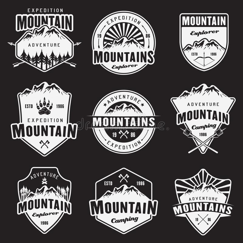 Emblemi bianchi di vettore di viaggio della montagna su buio royalty illustrazione gratis