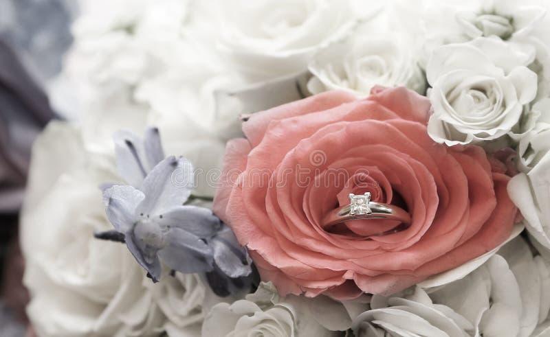 Emboîtement de bague de fiançailles dans le bouquet du ` s de jeunes mariées des fleurs photos libres de droits