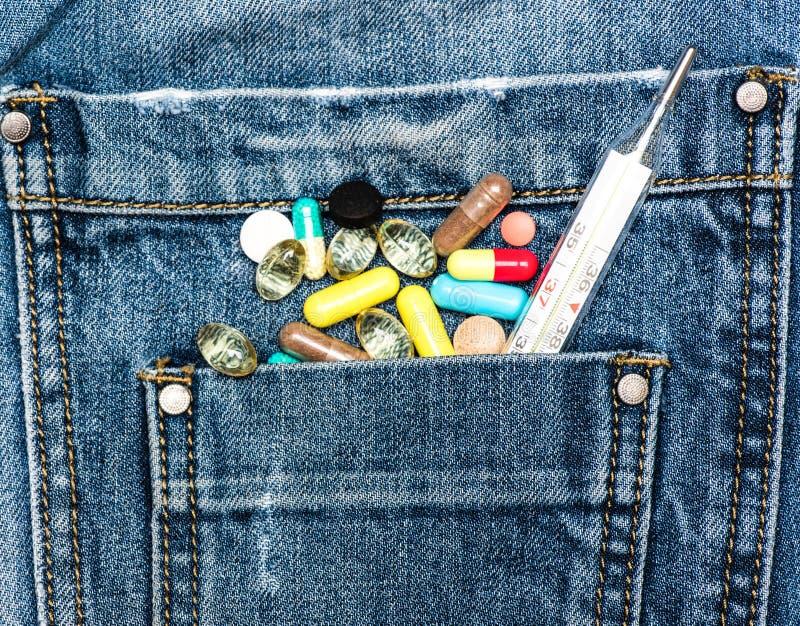 Embolse con las píldoras y el termómetro de mercurio coloridos como símbolo de la diversidad de las píldoras del pecho de medicin imagen de archivo libre de regalías