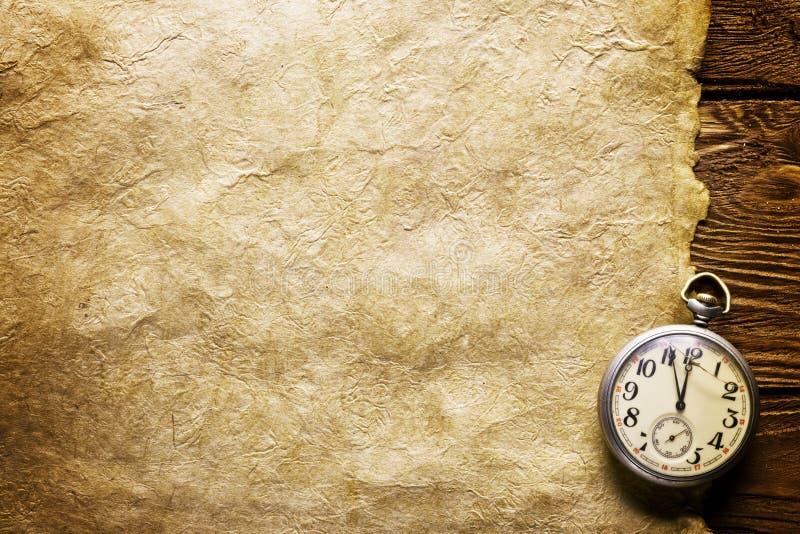 Embolse el reloj en el papel viejo foto de archivo