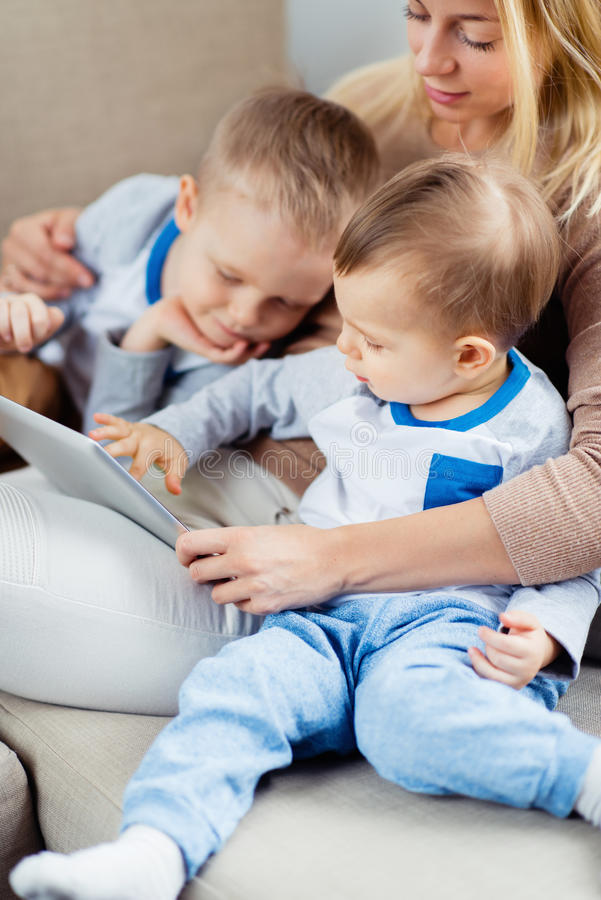 embosoming两个儿子的年轻母亲演奏数字式片剂 免版税库存图片