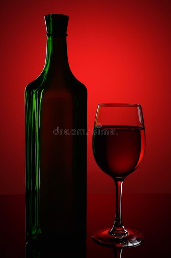 Embotelle y un vidrio de vino en un fondo rojo imagen de archivo