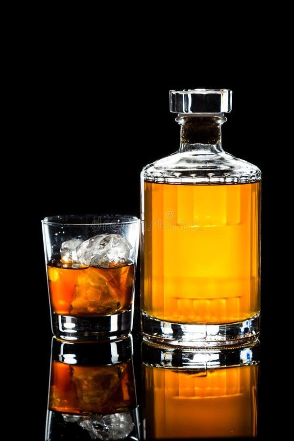 Embotelle y un vidrio de whisky en la roca contra un fondo oscuro foto de archivo