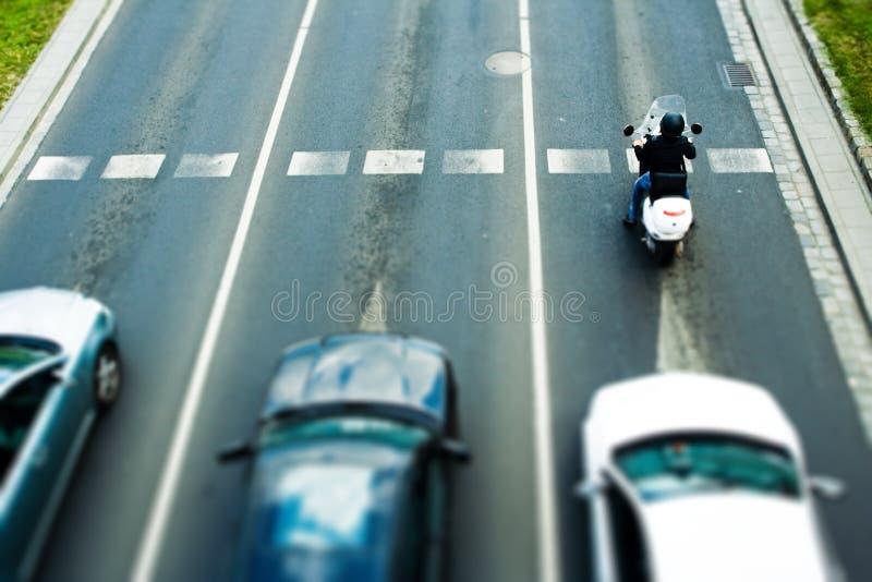 Embouteillage et femme sur le vélomoteur photo libre de droits