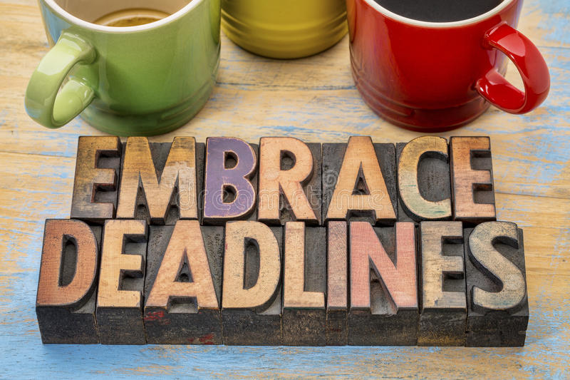 Embrace deadlines in wood type. Embrace deadlines - word abstract in vintage letterpress wood type blocks with cups of coffee stock image