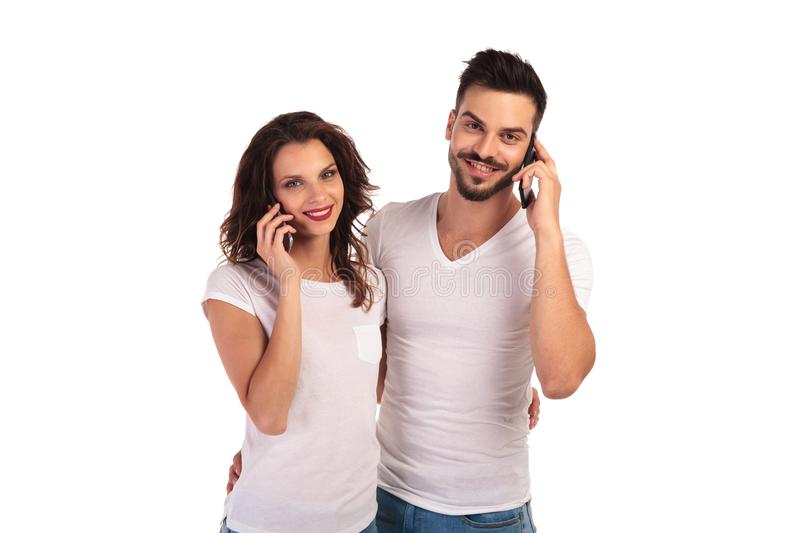 Embraced casual couple talking on the phone. On white background stock image