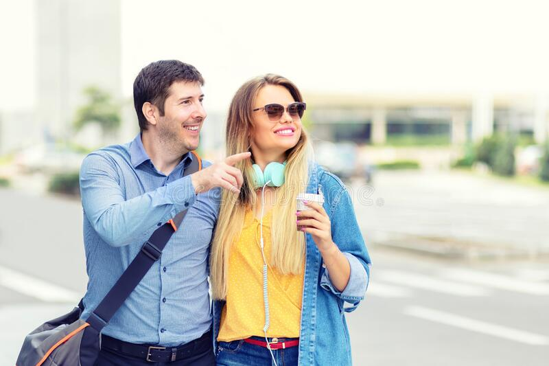 Embraced happy young couple enjoying weekend walk in city street stock image