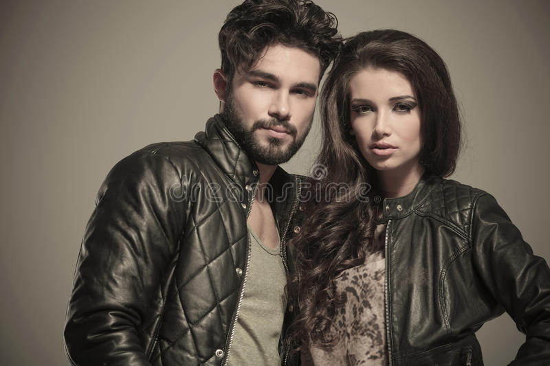 Embraced modern couple in leather jackets smiling. Closeup picture of an embraced modern couple in leather jackets smiling stock photography