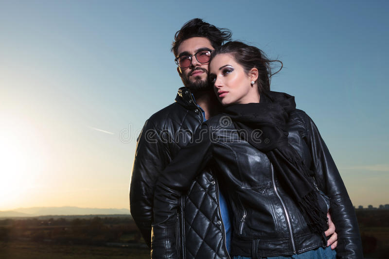Embraced romantic couple in the dawn. Embraced romantic couple posing against blue sky in the dawn stock photography