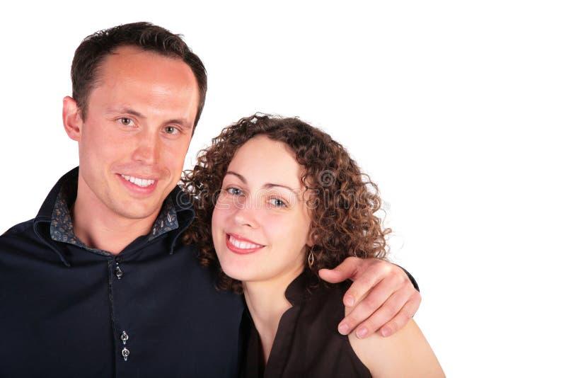 embraces спаривают усмешки молодые стоковое фото