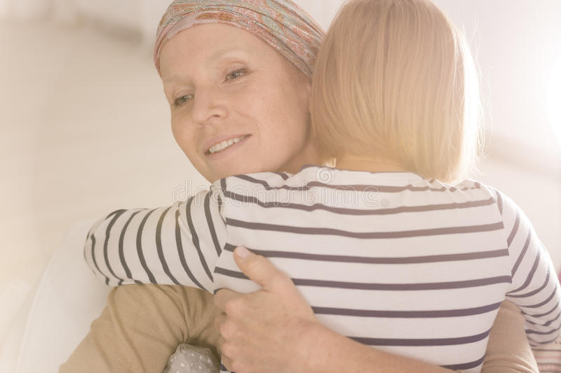 Embracing mother suffering from leukemia. Little caring girl embracing mother suffering from leukemia disease stock images