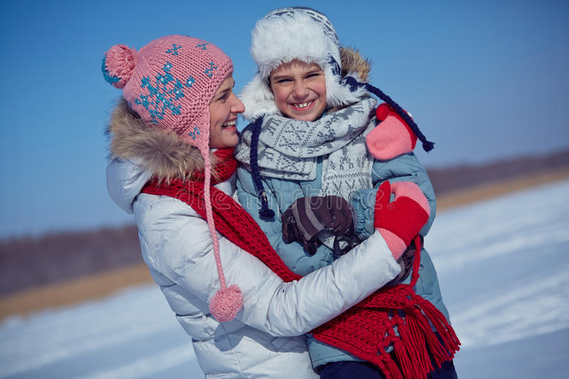 Embracing son. Pretty women embracing her little son outdoors on winter day royalty free stock photography