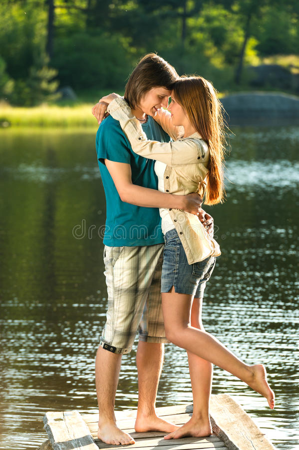 Embracing Teens Standing Barefoot On Pier Stock Photo