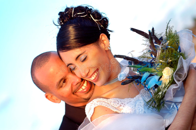 Embracing wedding couple. Young hispanic couple on wedding day outdoors - just married royalty free stock photo