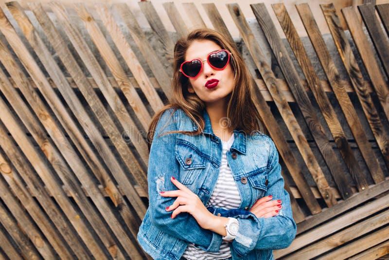 Embrassant les verres de port de coeur de fille avec de longs cheveux et bras pliés sur le fond en bois Portrait en gros plan de  image libre de droits