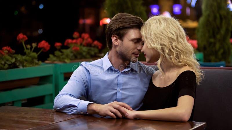 Embrassement tendre de couples avec sensibilité, se reposant en café ouvert de terrasse, unité photos libres de droits