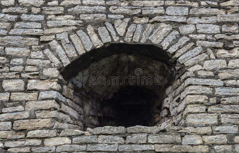Embrasure in der alten grauen Steinwand stockfotografie