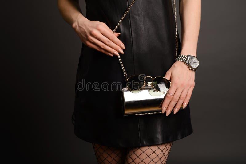 Embreagem da prata da posse da mulher da forma na bolsa e no relógio perto do fundo foto de stock