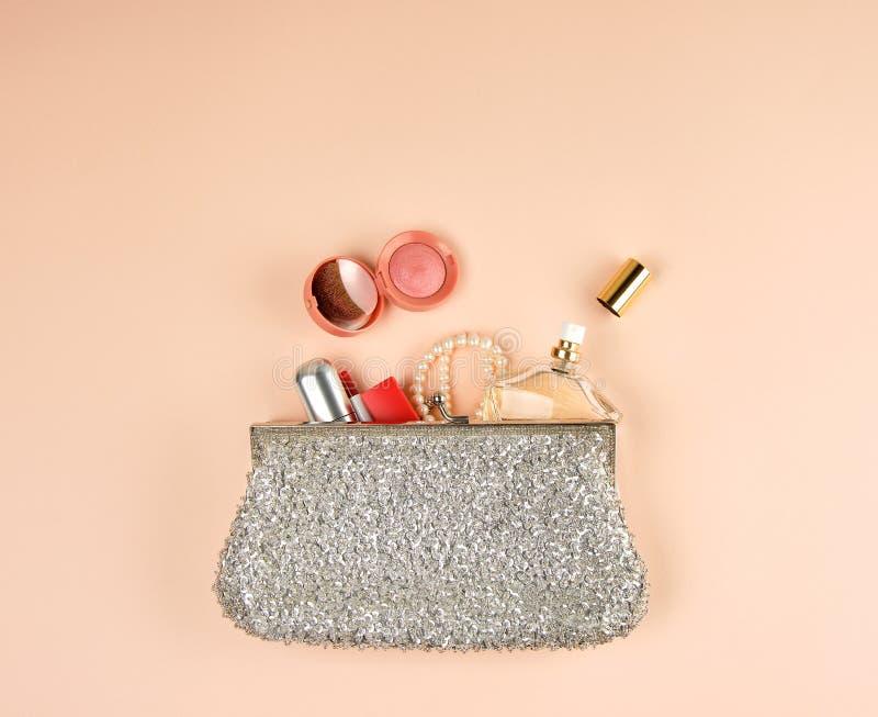 a embreagem e os cosméticos de prata abertos caíram fora do meio fotografia de stock royalty free