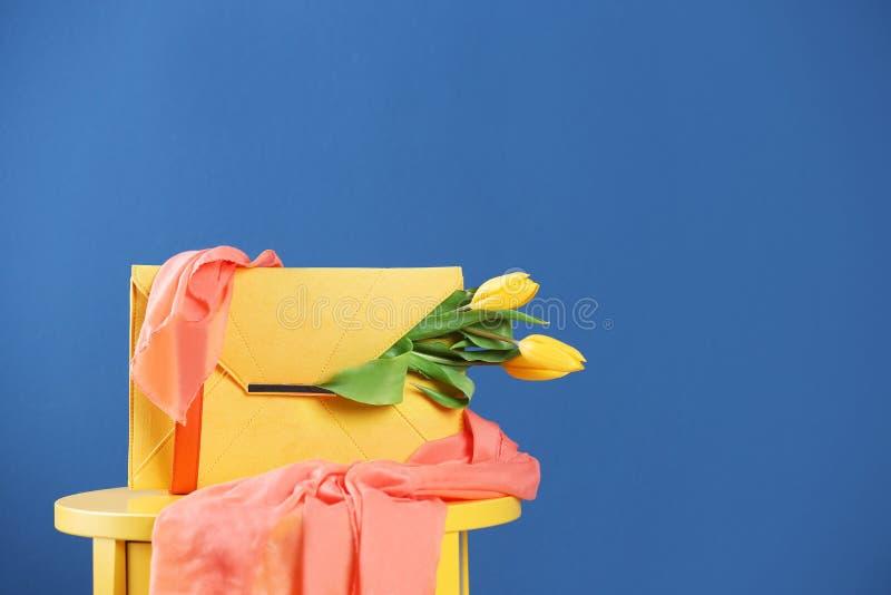 Embreagem elegante com flores e lenço da mola na tabela contra o fundo azul imagens de stock royalty free