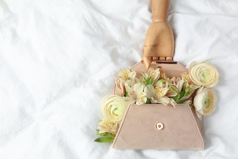 Embreagem ? moda com flores da mola e m?o de madeira na folha amarrotada, configura??o lisa do manequim foto de stock royalty free
