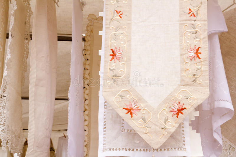 Embroided warm tablecloth with flowers. Embroided tablecloth with flowers hanging in outdoor market shop royalty free stock image