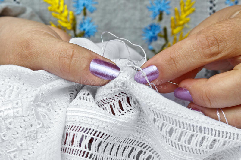 Embroider. A close-up of a woman embroidering onto linen stock photos