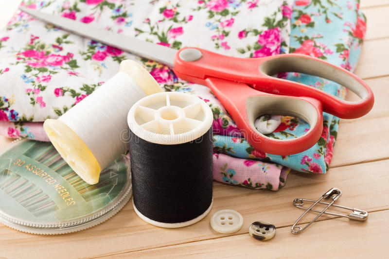 Embroider. Still life photography : fabric with old scissors, bobbin, neddles, safety pin and button in embroider concept royalty free stock photo