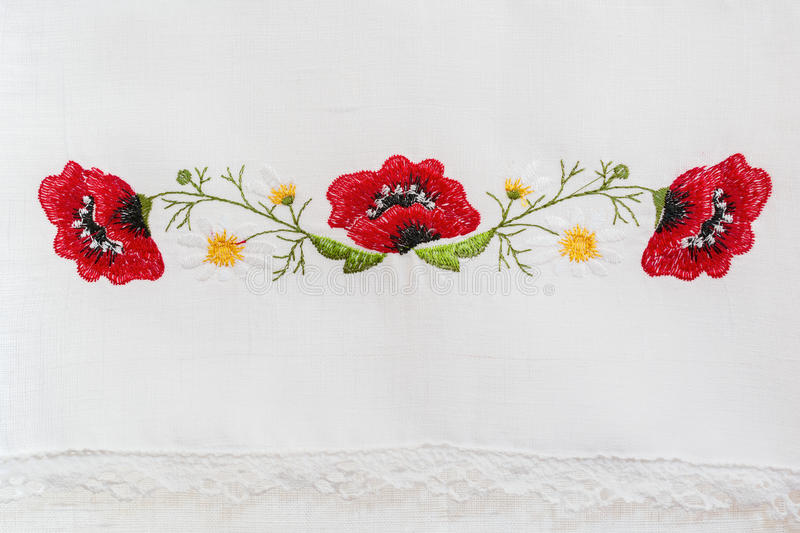 Embroidered floral pattern. On a white linen towel stock photo