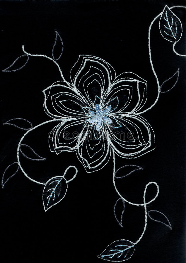Embroidered flower. White embroidered flower on black background stock photos