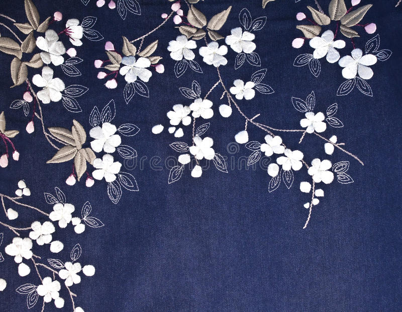 Embroidered flowers on denim. Embroidered Flowers, leaves, and stems on denim fabric royalty free stock images