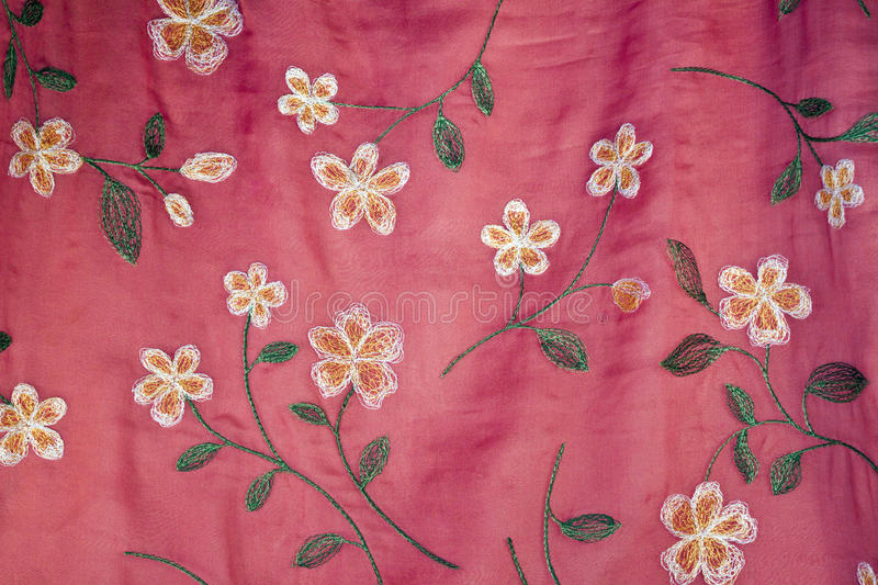 Embroidered Flowers on Pink Silk. Embroidered flowers, leaves, stems on pink silk royalty free stock photography