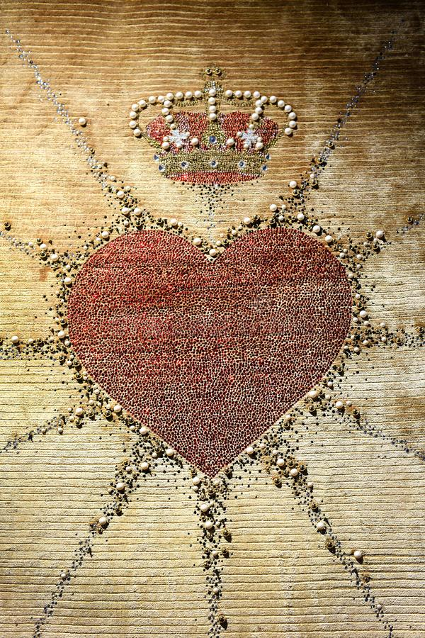 Embroidered heart and heraldic crown on tapestry stock images