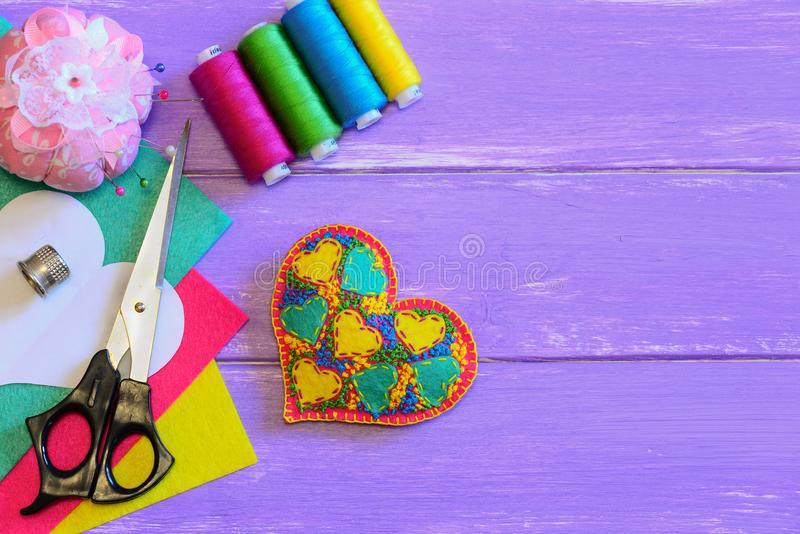 Embroidered heart ornament for Valentines Day. Felt heart ornament, thread set, scissors, pin cushion, colorful felt sheets royalty free stock photography