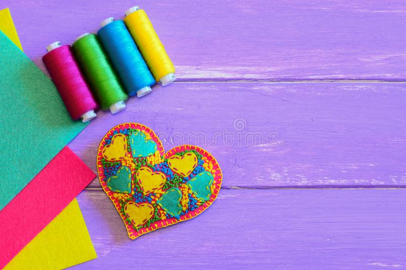 Embroidered heart for Valentines Day. Felt heart ornament, thread set, colorful felt sheets on a purple wooden background royalty free stock photos