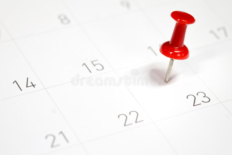 Embroidered red pins on a calendar on the 23rd. With selective focus royalty free stock photo