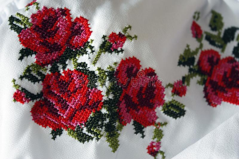 Embroidery with beautiful colorful red roses and green leaves, closeup. Cross-stitch texture, folk costume stock images