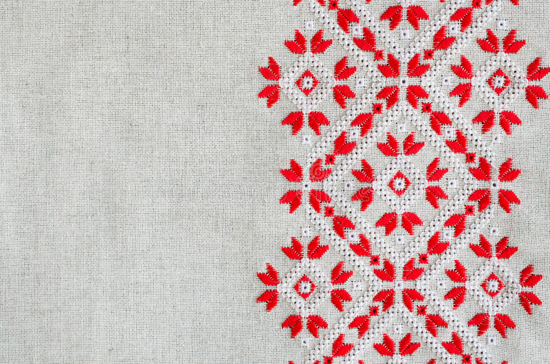Embroidery design by red and white cotton threads on flax. Christmas background with embroidery. royalty free stock image