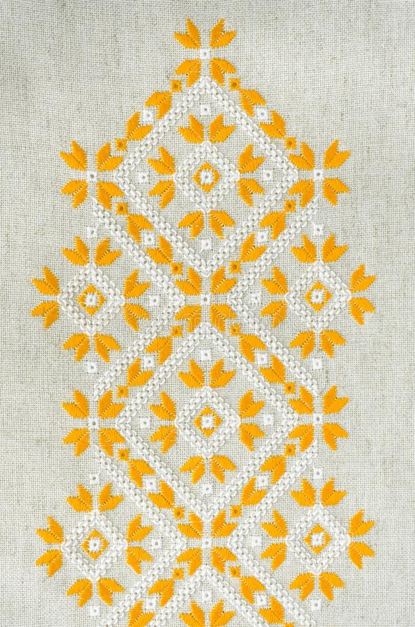 Embroidery design by yellow and white cotton threads on flax. Background with embroidery. stock photos