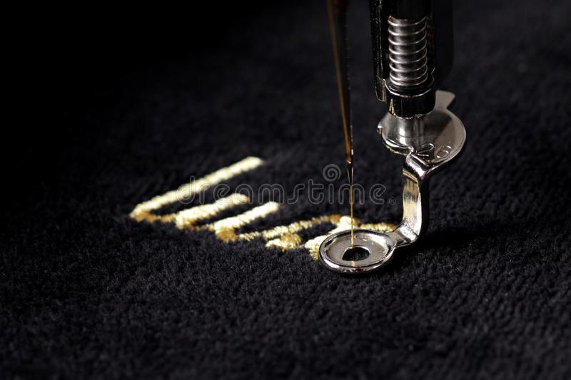 embroidery of gold lettering & x22;luxury& x22; on black velvety fabric with embroidery machine royalty free stock photo