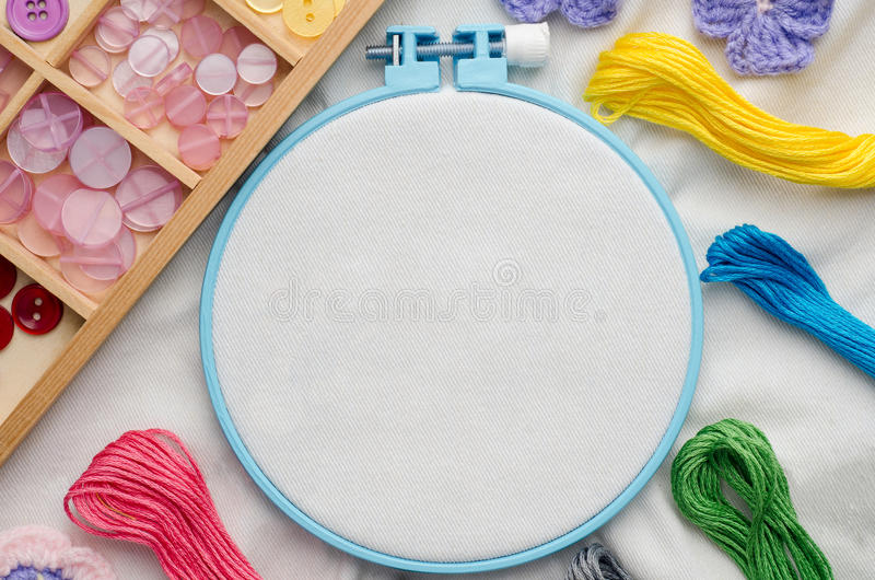 Embroidery hoop with blank fabric, colored sewing threads stock photos